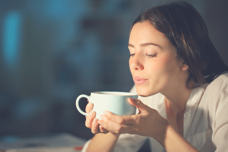 Woman blowing to cool hot coffee in the night at home, how to cool coffee fast
