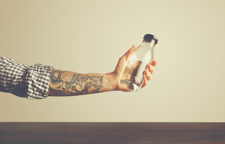 hand holds bottle with clean water, instant coffee dissolve in cold water