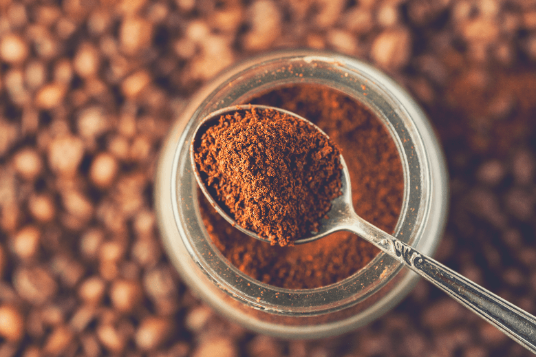 Ground coffee in a metal spoon on a top of glass jar, shallow depth of field, how to prevent coffee from hardening