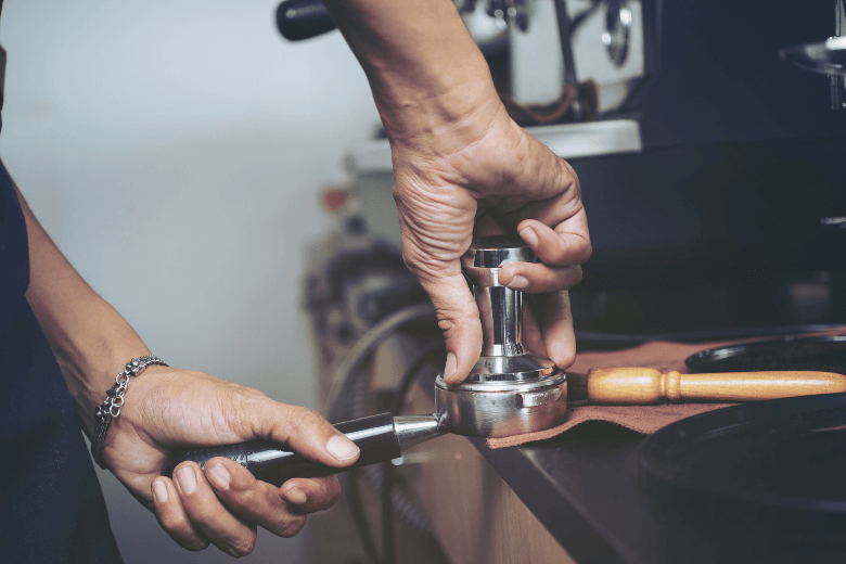 Selective focus Barista holding portafilter and coffee tamper making an espresso coffee at cafe,color vintage style, can you tamp coffee too hard