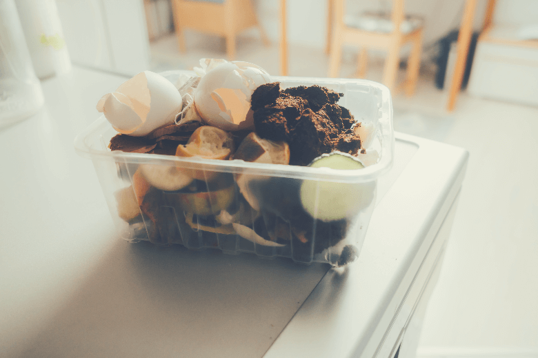 organic waste in a small plastic box, coffee grounds down the garbage disposal