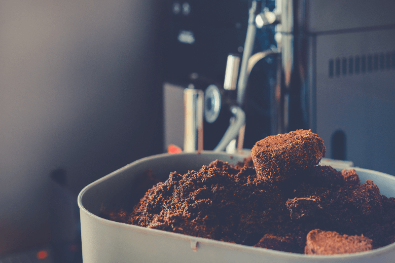 Used coffee grounds from espresso machine. Recycling compost container filled with used coffee waste. Coffee machine cleaning, coffee grounds down the garbage disposal