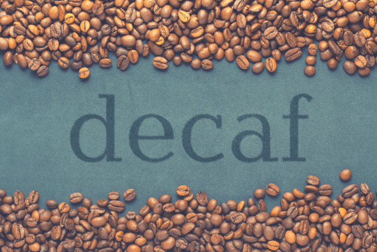 Closeup of coffee beans on grey background with the inscription decaf, best decaf coffee beans