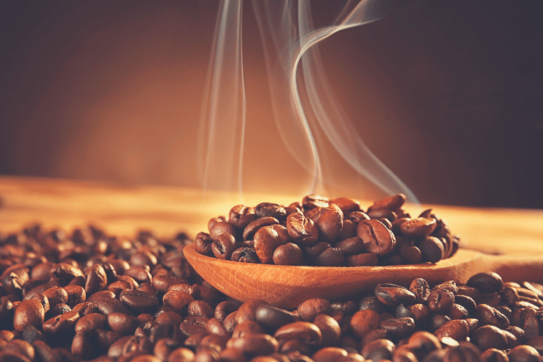 Wooden spoon with roasted coffee beans on blurred background, can you eat coffee beans