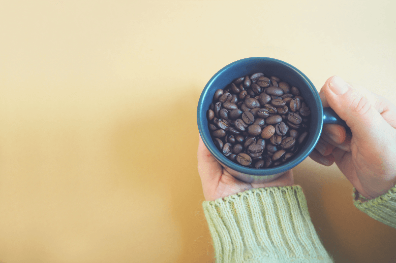 a woman in a beige wool sweater holds a dark gray mug with whole coffee beans on a brown background. top view. copy space, what is whole bean coffee