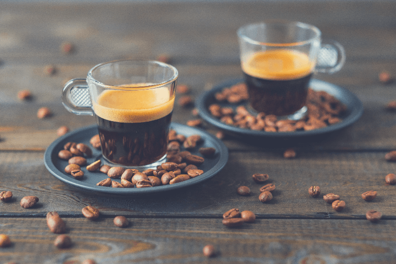 Two cups of espresso and coffee beans on a wooden table, can you use coffee beans for espresso