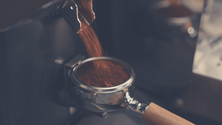 Closeup of grinding fresh coffee into pottomless portafilter, how to grind coffee beans for espresso